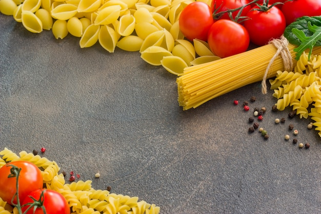 Frame with spaghetti and various ingredients for cooking pasta on a dark table, top view