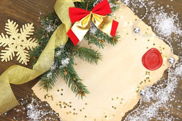 Рамка с винтажной бумагой и рождественскими украшениями на деревянных фоне