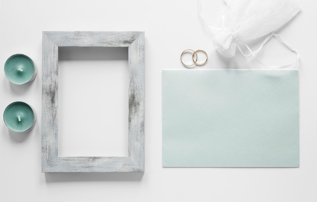 Frame with wedding card on table