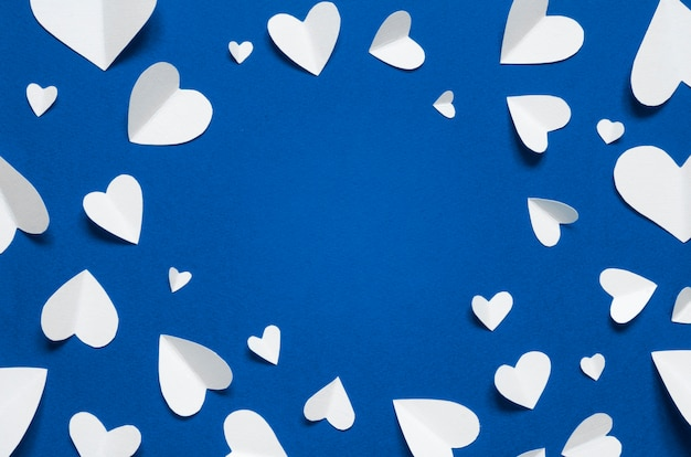 Frame with white paper hearts at blue backdrop, top view. color of the year 2020 classic blue. copy space..