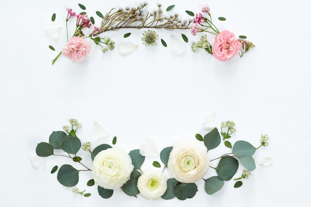 Frame with white ranunculus flowers on white background. flat lay, top view.
