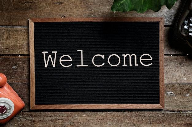 Frame with word welcome on wooden table