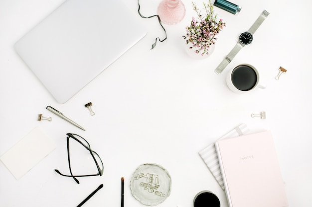 Frame of woman modern home office space with laptop, pastel pink notebook, glasses, coffee cup, wild flowers and accessories on white desk. flat lay, top view
