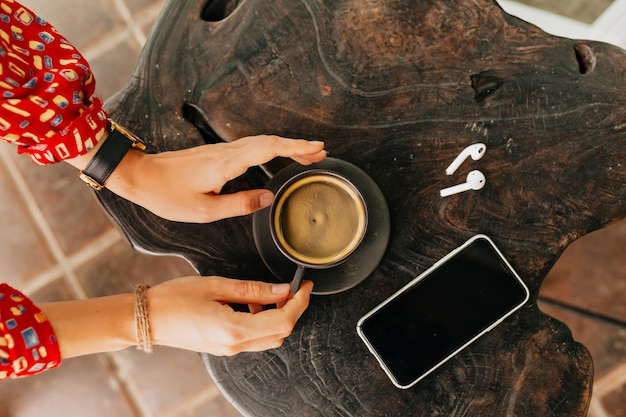 Sopra il telaio della mano della donna che tiene una tazza di caffè con le cuffie e lo smartphone