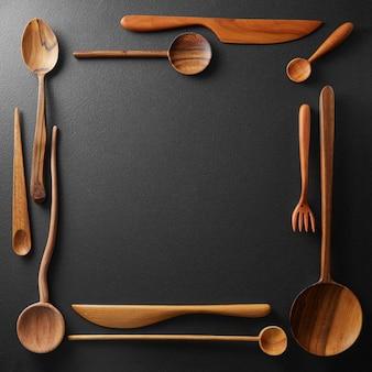 Frame of wooden kitchen utensil on black background