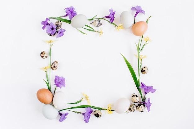 부활절 달걀, 메추라기 달걀, 흰색 표면에 노란색과 보라색 꽃으로 만든 프레임 화환