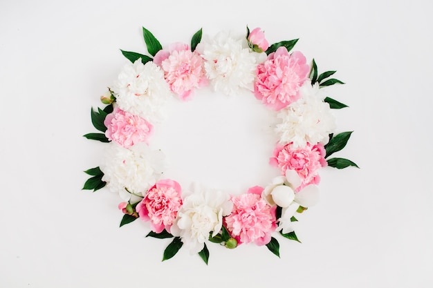 Frame wreath of pink peony flowers, branches, leaves and petals with space for text on white background. flat lay, top view