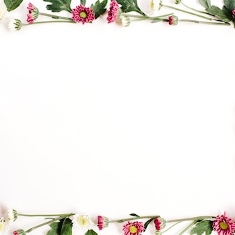 Frame wreath with red and white wildflowers, green leaves, branches on white surface