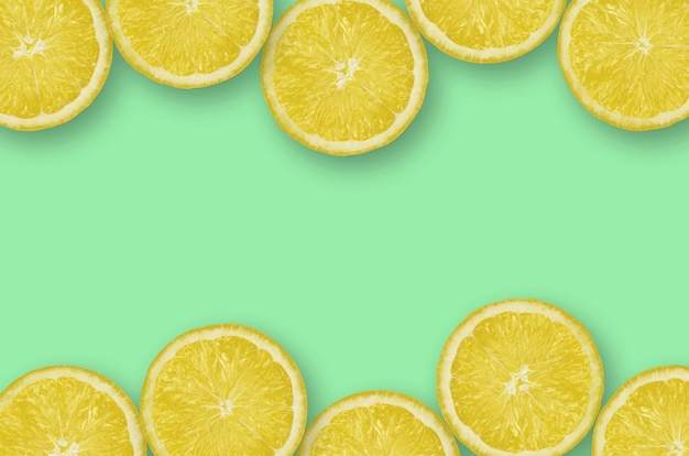 Frame of yellow lemon citrus slices on bright lime background