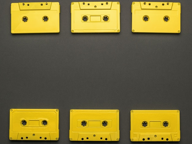 A frame of yellow tape cassettes on a black background. flat lay.