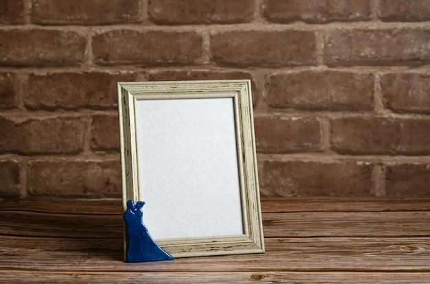 Обрамленная пустая карточка на деревянном столе с кирпичной стеной.