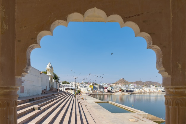 Framed view from archway at pushkar, rajasthan, india. temples, buildings and ghats on the holy water of the lake at sunset.
