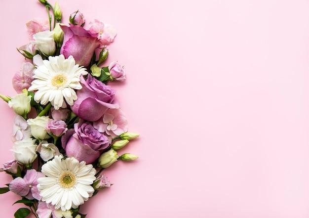 パステル調のピンクの背景の花のフレームワーク。フラット横たわっていた。