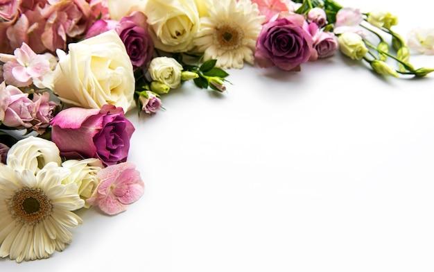 白い背景の花からのフレームワーク。フラットレイ。
