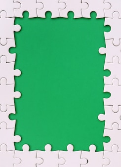 녹색 공간 주위에 흰색 직소 퍼즐로 만든 사각형의 형태로 프레임