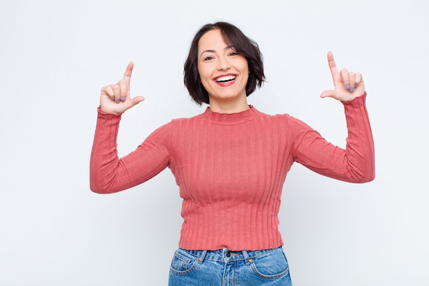 Framing or outlining own smile with both hands, looking positive and happy, wellness concept