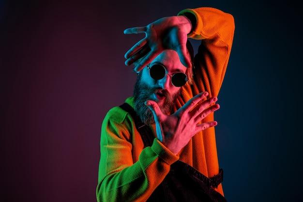Обрамление, селфи. портрет кавказского человека на фоне студии градиента в неоновом свете. красивая мужская модель с хипстерским стилем. концепция человеческих эмоций, выражения лица, продаж, рекламы.