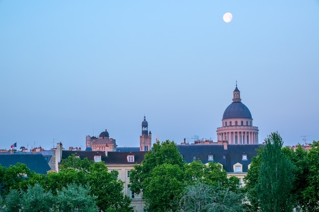 프랑스. 파리 지붕 위의 초여름 아침. 푸른 하늘에 보름달