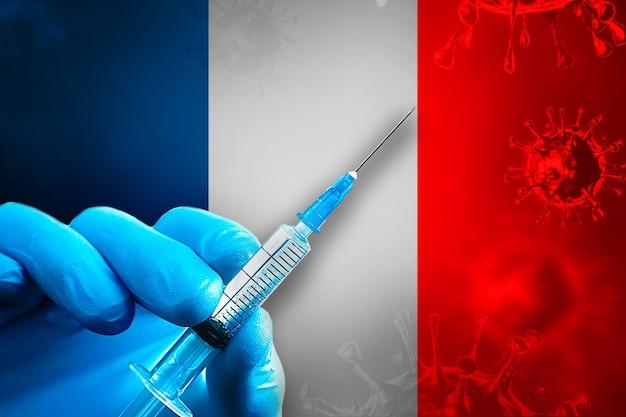 프랑스 covid19 예방 접종 캠페인 파란색 고무 장갑에 손이 깃발 앞에 주사기를 들고 있습니다