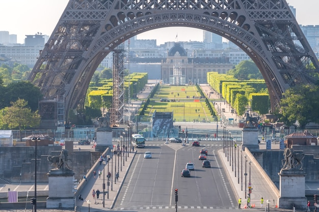 France. eiffel tower and champ de mars in paris. few tourists and cars on the jena bridge on a sunny summer morning