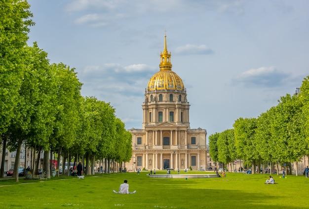 Франция, париж. часовня святого людовика инвалидов (место захоронения наполеона). люди отдыхают на зеленой лужайке