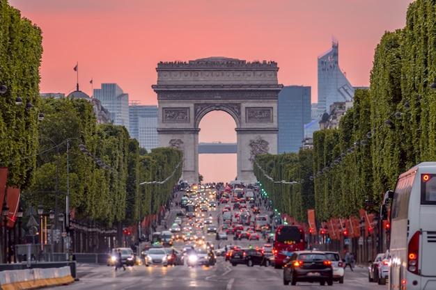 フランス。パリ。シャンゼリゼ通りの渋滞。凱旋門。ピンクの夕日