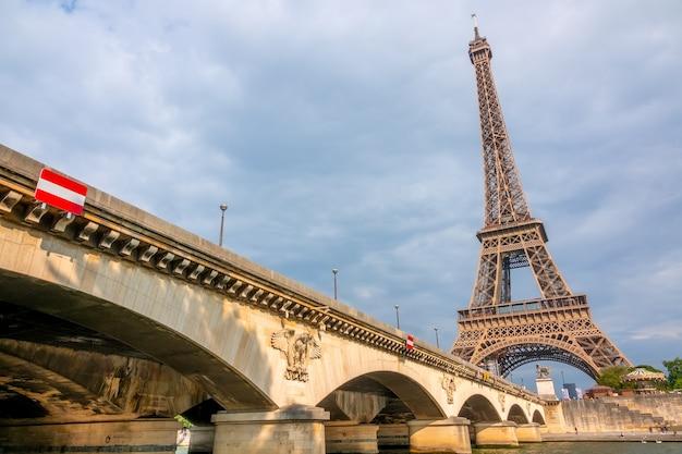 Франция, париж. эйфелева башня в пасмурную погоду и мост иена на солнце. вид снизу