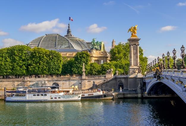 フランス。パリ。壮大な宮殿の屋根、セーヌ川のボート、アレクサンドル3世橋