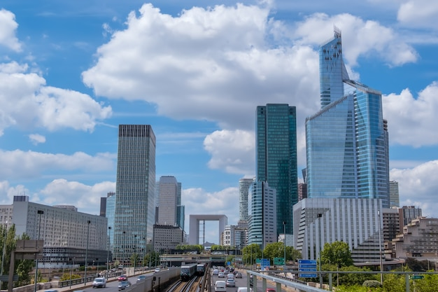 Франция. париж. современный район ла дефанс. автомобильный трафик, небоскребы и облака
