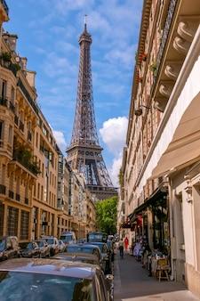 Франция. париж. узкая городская улица в летнюю солнечную погоду. эйфелева башня