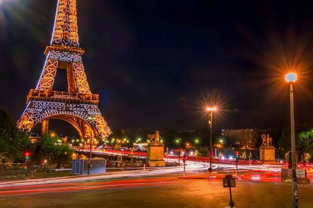 フランス、パリ。夜の交通と明るいエッフェル塔