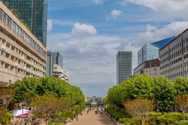 Франция. париж. пешеходная часть района ла дефанс. небоскребы и облака