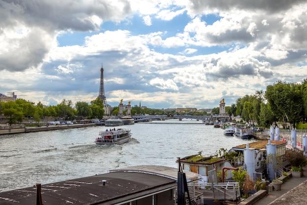 Франция, париж. летний день. река сена с видом на эйфелеву башню. многие дома на воде пришвартованы у гранитных набережных.