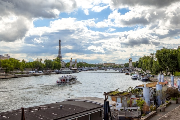 France, paris. summer day. river seine with a view of the eiffel tower. many houses on the water moored at granite embankments