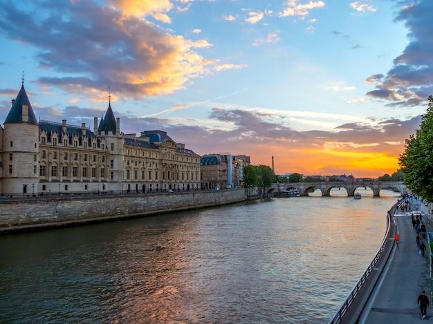 フランス。パリ。セーヌ川の橋に架かる夏の夜と日没。人々は遊歩道を歩きます