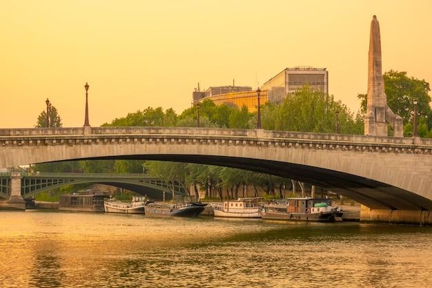フランス、パリ。セーヌ川の橋を渡る夏の夜。住宅のはしけは川岸に係留されています