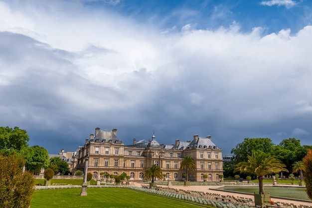 France. paris. summer in the luxembourg garden. sunny day. heavy rain clouds over the palace