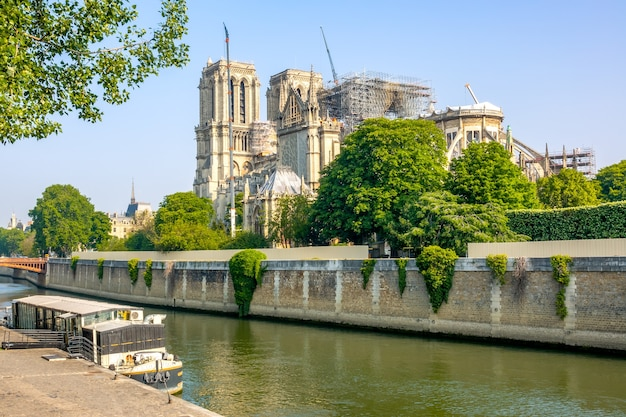 France, paris. summer sunny day. floating cafe on the river seine and renovation notre dame after a fire in the background