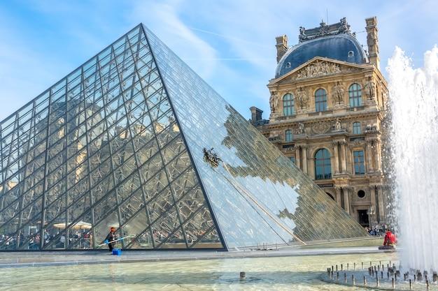 Франция, париж. летний солнечный день во дворе лувра. ручная и автоматическая промывка стеклянной пирамиды. фонтан и туристы