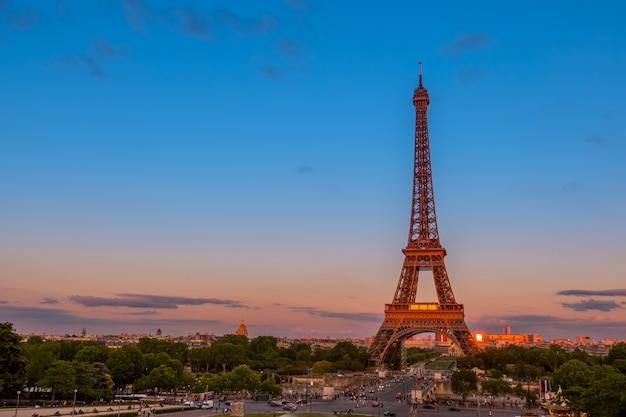 Франция, париж. летние сумерки. движение возле эйфелевой башни