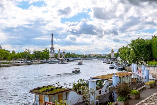 Франция. париж. солнечный летний день. водный транспорт на реке сена с видом на эйфелеву башню
