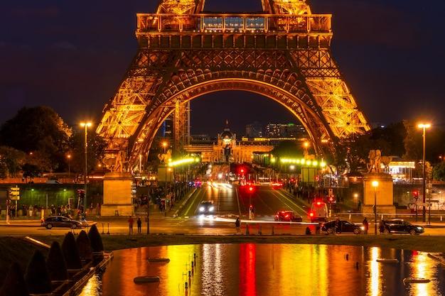 フランス、パリ。夜のイルミネーションが付いているエッフェル塔の近くの交通機関と観光客。トロカデロ庭園の障害者用噴水での反射