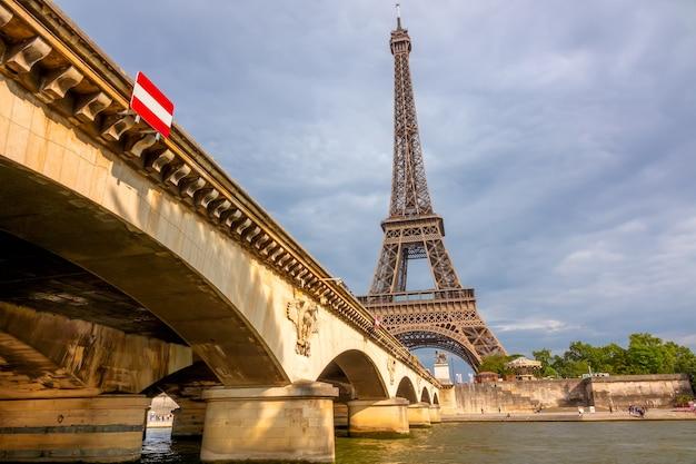 Франция. парижская эйфелева башня в пасмурную погоду и мост иена на солнце. вид снизу