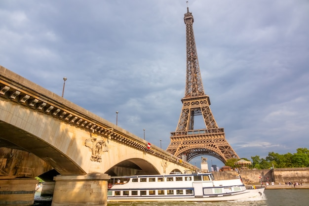 France. pleasure boat under the jena bridge, lit by the sun. eiffel tower on a background of cloudy sky