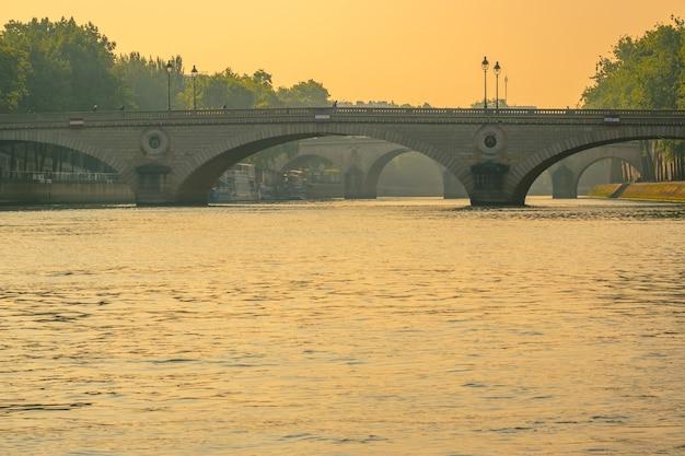 フランス。パリのセーヌ川と黄金の夕日に架かる石の橋