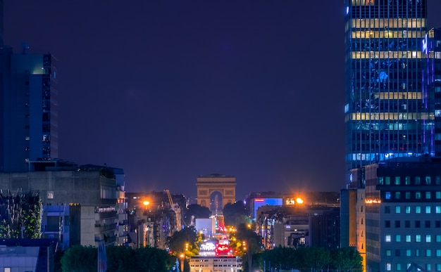 Франция. летняя ночь в париже. триумфальная арка в конце проспекта гранд-арми