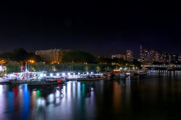 フランス。パリの夏の夜。セーヌ川の堤防には遊覧船が係留されています。色とりどりのライトがたくさん