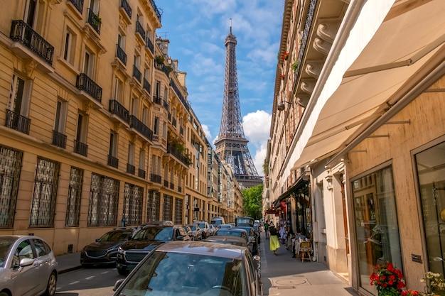 Франция. летний париж. солнечный день. много машин на узкой улочке. эйфелева башня на заднем плане
