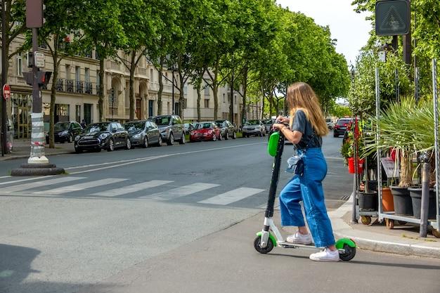 フランス。パリの夏の晴れた日。通りの交差点で電動スクーターの女の子
