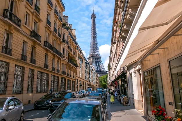 Франция. летний солнечный день в париже. много машин на узкой улочке. эйфелева башня далеко